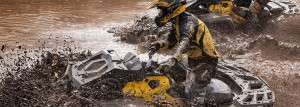 can-am outlander atv driving through deep mud